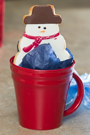 close up of holiday Christmas cookie in the shape of a snow man inside a red coffee cup