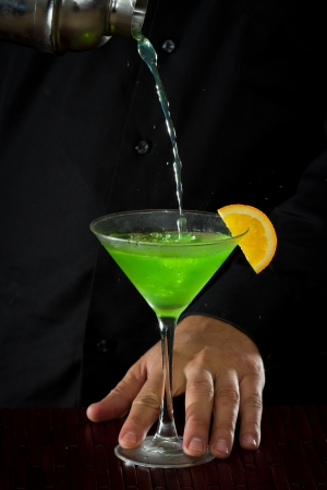 professional bartender pouring a green cocktail in to a martini glass with an orange slice garnish photo