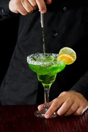 action shot: action shot of a bartender pouring a green margarita