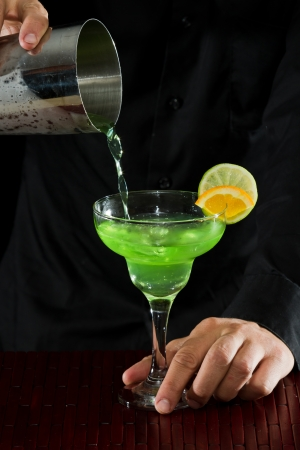 action shot of a bartender pouring a green margarita photo