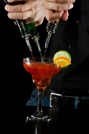 action shot of a bartender pouring red margarita using multiple bottles photo