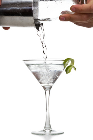 shaken: male hands pouring a vodka martini in to a chilled glass with a llime garnish