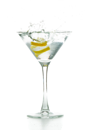 lemon twist falling in to a full martini glass isolated on a white