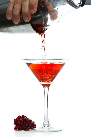 action shot: action shot of a bar tender pouring a pomegranate martini isolated on a white  Stock Photo
