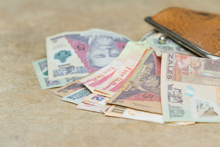 denominations: colorful bills from Guatemala and Belize spilling out of a leather bag on a counter top