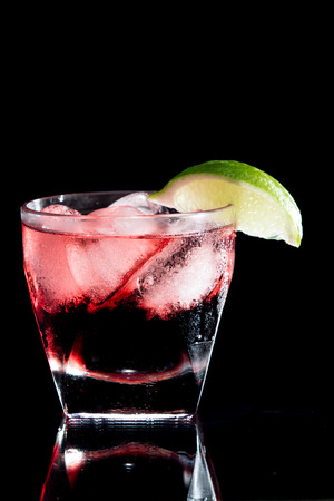 vodka and cranberry served on the rocks isolated on a black on a reflective surface garnished with a fresh lime slice photo