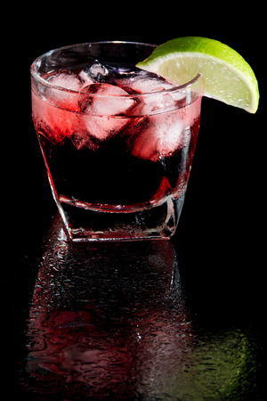 vodka and cranberry served on the rocks isolated on a black on a reflective surface garnished with a fresh lime slice