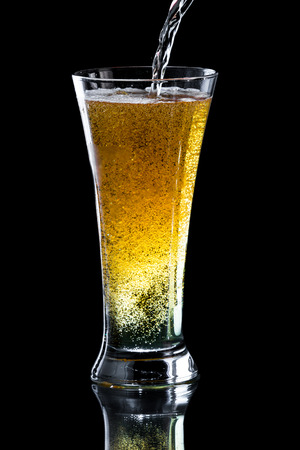 the carbonation: pouring an apple cider beer into a tall cold glass isolated on a black background