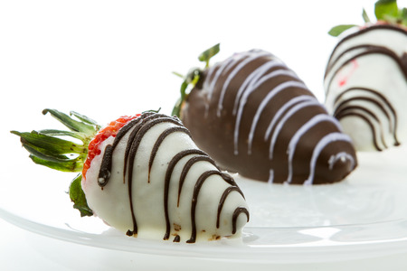 chocolate covered strawberries close up with white and dark chocolate isolated on a white background photo