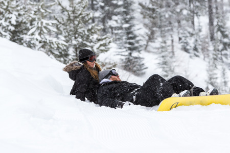 young couple with snowboards sitting on fresh snow in the mountains of northern Idaho photo