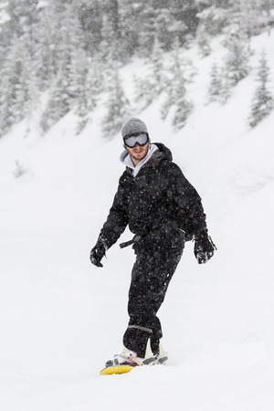 adult male snowboarding in the mountains of northern Idaho in snowy winter conditions photo
