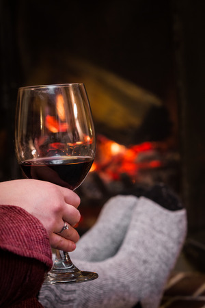 cold feet warming up in front of the fireplace with a glass of red wine photo