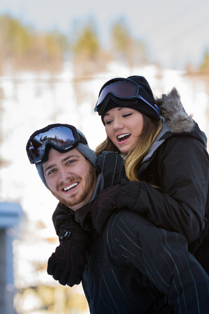 beautiful young couple wearing snow gear playing outside on the snowy mountains of northern Idaho photo