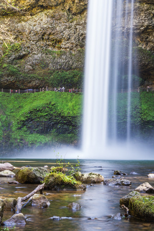 beautiful natural scene of silver lake falls in Oregon with blured people in the path behind them photo