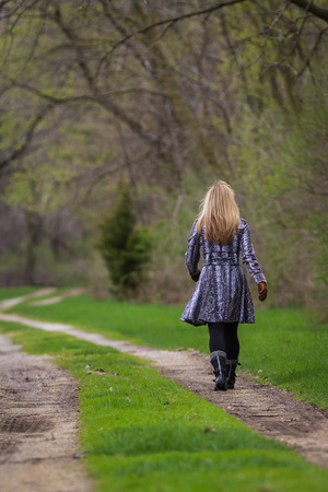 blonde fatale woman walking by her self on a dirt road in the woods photo