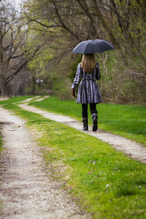 blonde fatale woman walking by her self on a dirt road in the woods with a black umbrella photo