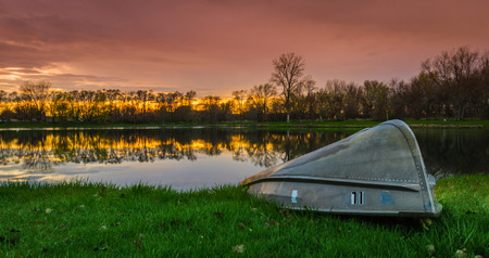 beautiful sunset with a reflection over a small lake in Illinois with a small row boat in the front