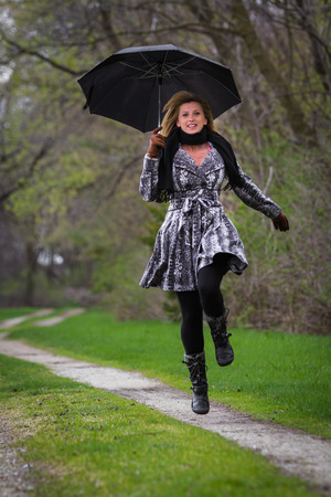 blonde fatale woman skipping and smiling holding a black umbrella on a dirt road photo