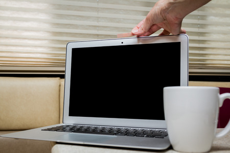 menselijke hand zetten een pleister op de webcam van de laptop in een thuissituatie Stockfoto