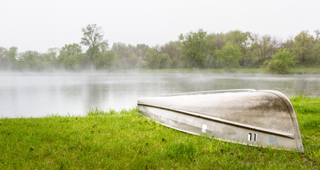 early morning fog lingering over the lake with vivid green trees surrounding it and a small fishing boat Stock fotó