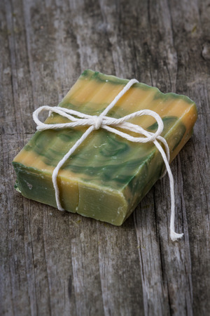 freshly made organic bar of lemongrass soap on an old wooden table