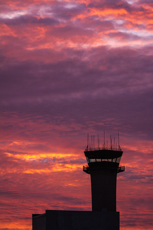early morning at the airport with beautiful color clouds behind the control tower