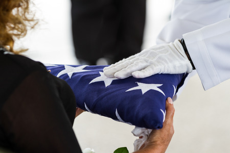 active navy representatives giving the US flag to the widow at a veterans funeral Archivio Fotografico