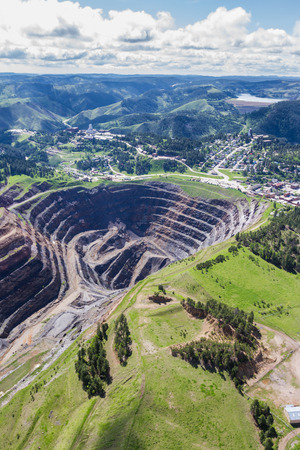 aerial view of an abandoned open pit mine and the town of Lead, South Dakota Stock Photo