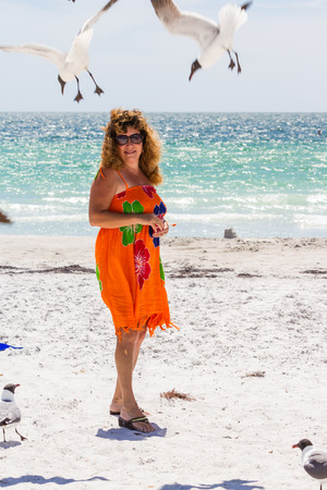 female tourist standing on the beach with seagulls flying around her with the ocean on the background photo