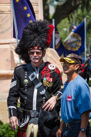 Bay Pines, Florida - May 26 : Bagpiper and navy veteran posing for a photo after the Memorial Day parade, May 26 2014 in Bay Pines VA cemetery in Florida