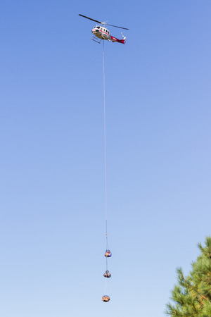 Prospect Oregon  - September 9 : Helicopter mid air with an extended cable bringing supple sot and from the 790 fire,September 9 2014 in ProspectOregon