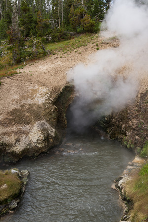 water feature: active cave in yellowstone national park with steam and water flowing constantly with extremely hot temperatures