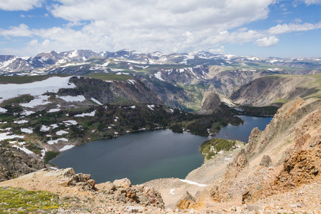 caped: mid july mountain landscape in Montana with snow caped mountains and lakes at high elevations Stock Photo
