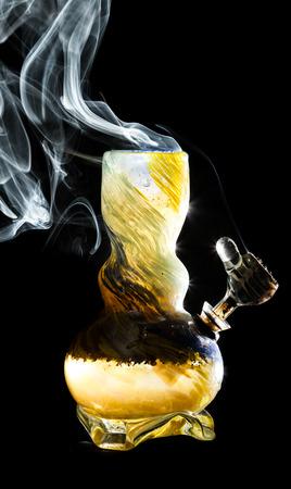 bong: high contrast studio shoot of a bong with simulated marijuana smoke on a black background