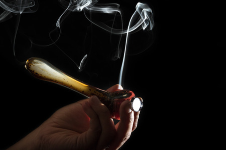 high contrast studio shoot of a pipe with simulated marijuana smoke on a dark background