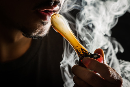 drug use: studio shoot with model simulating smoking pot with a pipe in a dark high contrast image