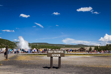 Yellowstone national park, Wyoming - July 22 : group of tourists standing watching old faithful geyser; July 22 2014 in Yellowstone national park, Wyoming