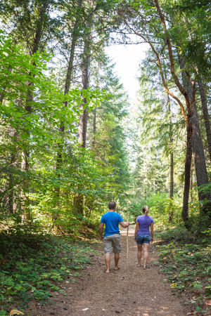 young couple walking in the Oregon forest with vivid green vegetation