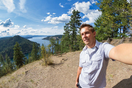 young man portrait in form of a selfie over Coeur d Alene lake, Idaho, from the top of mineral ridge photo