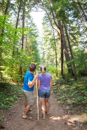 young couple walking in the Oregon forest with vivid green vegetation photo