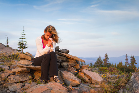 oneness: beautiful woman praying on the top of a mountain Stock Photo