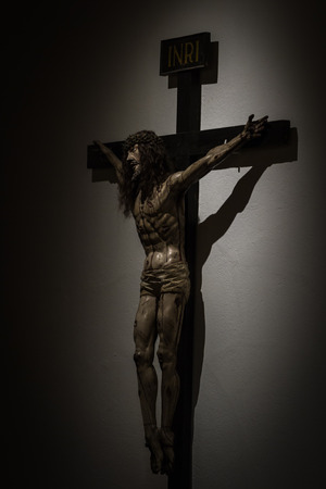 close up with dramatic light on a statue of Jesus Christ on a cross photo