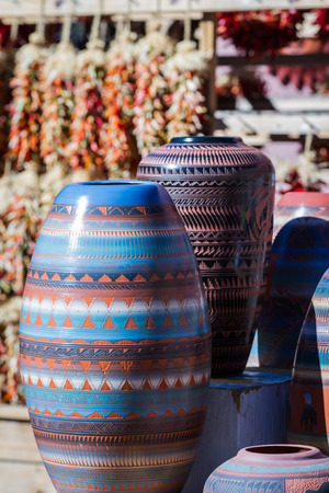 southwestern pottery in a shop in Santa Fe New Mexico with chilies hanging on the background