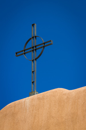 close up of a Christian cross on top of a church with the traditional southwestern architecture