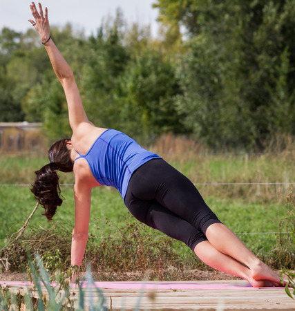 young beautiful woman practicing the art of yoga on an outdoors setting photo