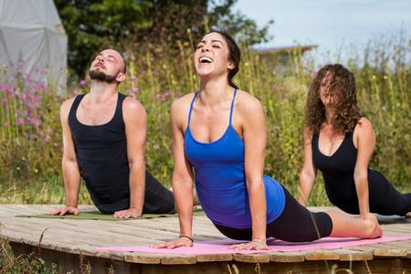 or instruction: group of young people practicing in an outdoor yoga class