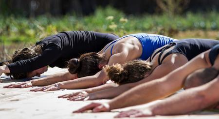 clases: grupo de j�venes que practican en una clase de yoga al aire libre Foto de archivo