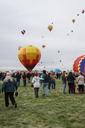 Albuquerque New Mexico - October 8 : Hot air balloons lifting off in with families and crews enjoying the Ballon Fiesta show, October 8 2014 in Albuquerque, New Mexico