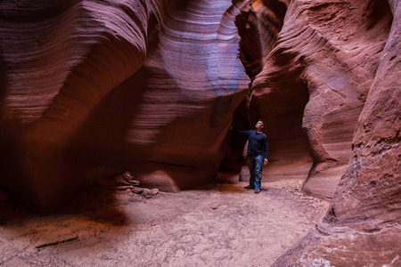 slot canyons: young man exploring slot canyons in Page Arizona with beautiful shades of red and orange Stock Photo