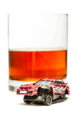 under the influence: DUI concept. Image of a drunk driving accident inside a small glass with beer isolated on a white background